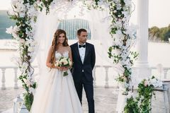 Attractive groom and bride at wedding day ceremory with arch and lake on background stands together. Beautiful newlyweds. Young women in white dress and long Royalty Free Stock Photo