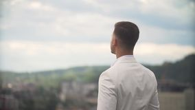 Attractive groom in white suit is coming on the terrace and enjoying the charming landscape alone. stock video