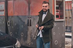Attractive man is posing with hose at car-washing station near his car. royalty free stock photography