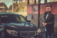 Attractive man is posing with hose at car-washing station near his car. royalty free stock photo