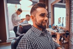 Attractive groomed man is sitting while waiting for a barber at busy barbershop. Attractive groomed men is sitting while waiting for a barber at busy barbershop royalty free stock image