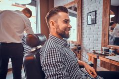 Attractive groomed man is sitting while waiting for a barber at busy barbershop. Attractive groomed men is sitting while waiting for a barber at busy barbershop stock images