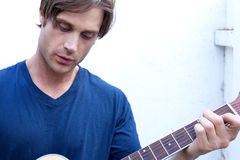 Attractive Guitar Player. An attractive guitar player with a blue shirt and white background Royalty Free Stock Photo