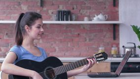 Attractive guitarist woman learning play stringed musical instrument uses laptop computer with online video teaching and. Enjoy music at home