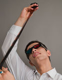 Attractive guy in 3D eyepieces with a film Stock Photography