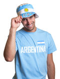 Attractive guy with argentinian jersey and hat laughing at camera Royalty Free Stock Photos