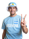 Attractive guy with argentinian jersey and hat showing victory sign Stock Image