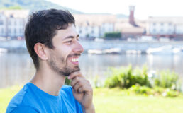 Attractive guy with beard and blue shirt looking sideways. Outside on a river with meadow and city scape on the background Stock Image
