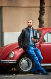Attractive guy holding camera, standing near red retro car. Attractive guy with a beard holding a camera in hand standing near a red retro car looking into the Royalty Free Stock Photography