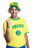 Attractive guy with brazilian jersey and hat laughing at camera Stock Photos