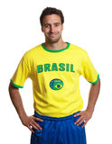 Attractive guy with brazilian jersey smiling at camera Stock Photos