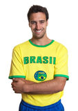 Attractive guy with brazilian jersey standing with crossed arms Stock Photos