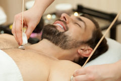 Attractive guy is getting massage at beauty salon Royalty Free Stock Photos
