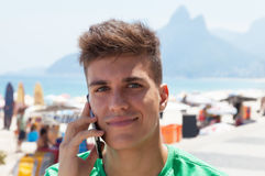 Attractive guy in a green shirt at beach speaking at phone Stock Images