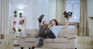 Attractive guy with his girlfriend moved in a new apartment they make some changes carrying the sofa in the middle of. Living room they excited take a sit on stock video