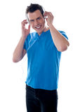 Attractive guy holding headphones. And listening to music Royalty Free Stock Photos