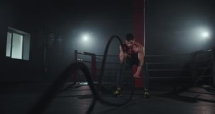 Attractive guy muscle body training in a cross fitness class using ropes concentrated doing his workout.  stock video footage