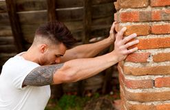 Attractive guy next to a brick wall. Attractive guy with white t-shirt next to a brick wall Royalty Free Stock Photo