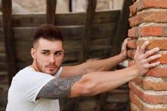 Attractive guy next to a brick wall. Attractive guy with white t-shirt next to a brick wall Stock Photos