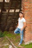 Attractive guy next to a brick wall. Attractive guy with white t-shirt next to a brick wall Stock Images