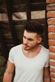 Attractive guy next to a brick wall. Attractive guy with white t-shirt next to a brick wall Royalty Free Stock Photography