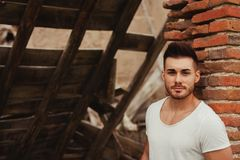 Attractive guy next to a brick wall. Attractive guy with white t-shirt next to a brick wall Stock Image
