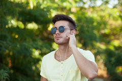 Attractive guy in the park with sunglasses listening music. Attractive guy in the park with sunglasses and yellow t-shirt listening music Royalty Free Stock Image