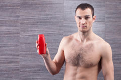 Attractive guy is presenting skin care product. This shower gel is for real men. Waist up portrait of cheerful young man showing a bottle. He is standing and Stock Photo