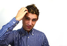 Attractive guy scratching his head. Good looking young man thinking Stock Photography