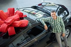 Attractive guy standing near big black auto with bow on top. stock image