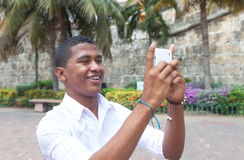 Attractive guy taking a picture with phone. In a colonial town with palms in the background Royalty Free Stock Photos