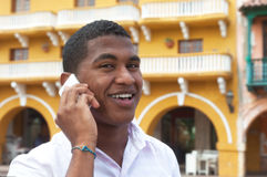 Attractive guy talking at phone in a colonial town. With historic buildings in the background Stock Photo