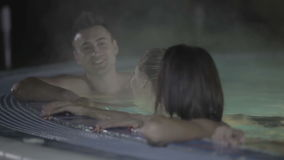 Attractive guy talking and relaxing with cute girls in the pool stock video