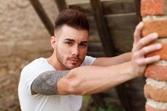 Attractive guy next to a brick wall Stock Photos