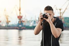Attractive guy working with camera. Young stylish photographer looking through camera during photo session with gorgeous stock images