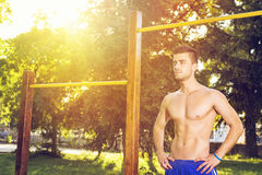 Attractive guy working out outdoors on a sunny summer day. Shirtless attractive fit young Caucasian guy working out outdoors on a sunny summer day Royalty Free Stock Photography