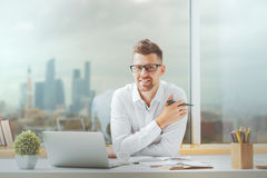Attractive guy working on project. Attractive young guy working on project at modern office desk Royalty Free Stock Photo