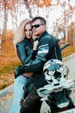 An attractive guy and a young woman in a black leather outfit with a motorcycle royalty free stock photo
