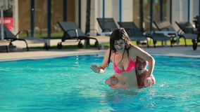 Attractive guy and young woman are having fun in the pool stock video footage