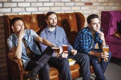 Attractive guys with glasses of beer watching TV royalty free stock photography