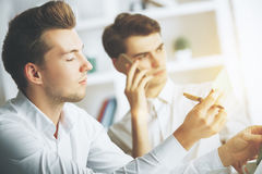 Attractive guys talking on phone. Close up portrait of two attractive european guys talking on phone at workplace Stock Photo