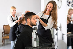 Attractive hairdresser making haircut on man Stock Photo