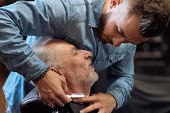 Attractive hairdresser is shaving male beard with the knife Stock Images