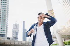 Attractive handsome asian man gets thirsty because of hot weathe royalty free stock photography
