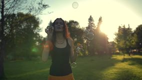 Attractive handsome female playing with soap bubbles, outdoor having fun stock footage