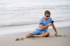 Attractive and handsome man on his 30s sitting on the sand relaxed on the beach laughing in front of the sea texting on mobile pho stock photo