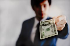 Attractive handsome young businessman is giving money or dollars stock photo