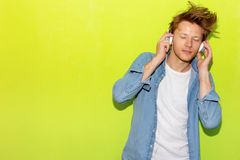 Attractive handsome young guy listening music by using headphone. Cool guy gets happy and relaxed. Charming handsome man love stock photos