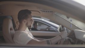 Attractive handsome young tattooed man in sunglasses sitting in luxury sport racing car opposite to rival ready to start. A car race on empty highway road stock footage