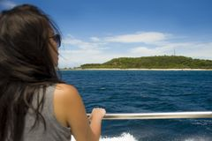 Attractive and happy Asian Chinese woman on excursion ship or ferry looking ocean and island enjoying sea breeze on summer holiday. Young attractive and happy Stock Photography